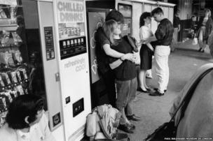 Two young couples embrace standing beside vending machines at Victoria Coach Station, c. 1990