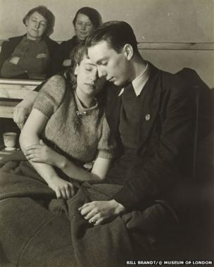 A young couple resting in an air raid shelter in North London