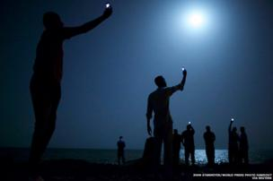 African migrants on the shore of Djibouti city at night, raising their phones in an attempt to capture an inexpensive signal from neighbouring Somalia