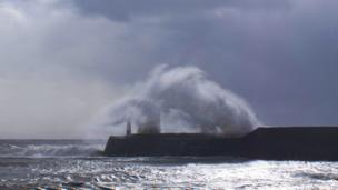 A wave leaps over Porthcawl lighthouse