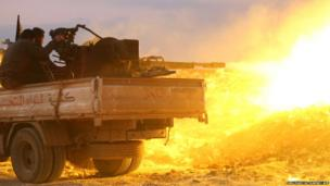 Rebel fighters fire a heavy machine-gun at the government forces Al-Samman checkpoint on a road leading to Idlib, near the Syrian city of Hama, on 17 February 2014