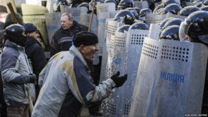 An anti-government protester reacts as he stands in front of police lines during clashes in Kiev