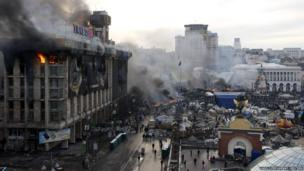 A trade union building is seen on fire in Independence Square as clashes continue in central Kiev