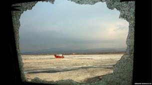 A boat is seen through the shattered window of an abandoned ship, both stuck in the salt of Lake Oroumieh