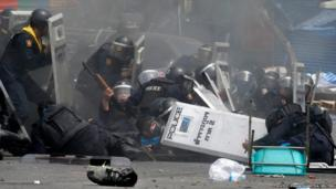 Thai police officers react after an explosion during clashes