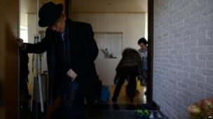 North Korean-born Kim Se-rim (L) leaves his house in Seoul as he prepares to make his way to a reunion of families from North and South Korea separated by the war, on 19 February 2014