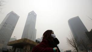 A woman wearing a mask makes her way amid the heavy haze in Beijing on 23 February 2014