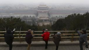 Residents stretch their legs during morning exercises on the top of Jingshan Park near the Forbidden City on a hazy day in Beijing on 21 February 2014
