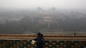 A security guard standing on top of a hill in Jingshan Park in haze-covered Beijing
