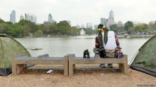 An anti-government protester keeps watch at a campsite in Lumpini Park in Bangkok