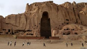 Afghan boys play football in front of the empty seat of one of two Buddha statues, destroyed by the Taliban in 2001, in Bamiyan province
