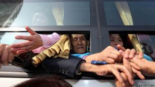North Koreans on a bus hold their South Korean relative's hands after the Separated Family Reunion Meeting at Diamond Mountain