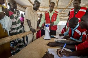 Matiop (wearing wristwatch) registers his family with Uganda Red Cross volunteers.