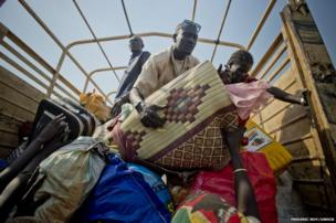 Matiop's wife hands a sleeping mat to him on a truck, one of many shuttling 100 people at a time away from the South Sudan border.