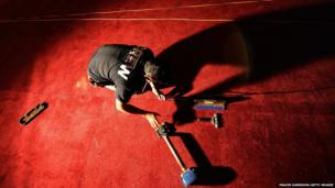 A man installs the red carpet for the Oscars