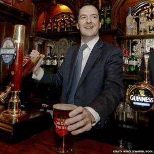 Britain's Chancellor of the Exchequer George Osborne pulls a pint of beer at the Red Lion pub in London