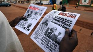 A man holds up daily newspapers in Bangui