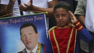 A boy wearing an historical uniform stands next to a poster of the late President Hugo Chavez during a military parade commemorating the one year anniversary of Chavez's death on 5 March, 2014