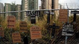 Cardboard cut-outs in shapes of headstones and crosses and tied to a fence, bear anti-government protest slogans and names of those who have died in recent protests, in Caracas on 5 March, 2014.