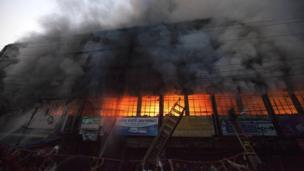 Firefighters tackle a blaze at a garment factory in Dhaka, Bangladesh