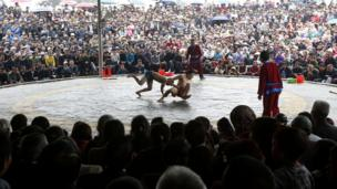 Villagers brave the rain to watch a wrestling match during the Chua Nanh festival in a village near Hanoi, Vietnam
