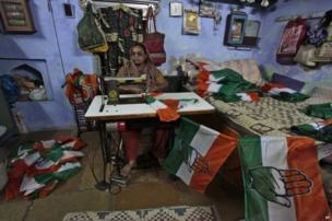Indian woman stitches Congress party flags ahead of parliamentary elections in Ahmedabad.