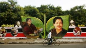 A cyclist rides past pictures of Tamil Nadu state chief minister and All India Anna Dravida Munnetra Kazhagam (AIADMK) leader Jayaram Jayalitha on the party symbol, two leaves displayed on a wayside in Chennai.