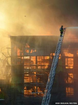 A firefighter battles flames at a building site in the China Basin area of San Francisco