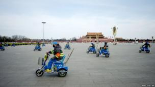 A group of cleaners pick up litter as they ride tricycles in Tiananmen Square, Beijing