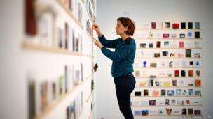 "Gloria Cevallos puts up postcards at the Royal College of Art's annual ""secret"" art exhibition"