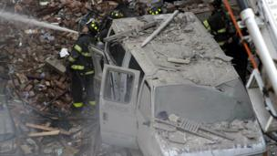 A firefighter directs a hose at the building from next to a damaged vehicle