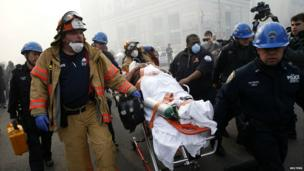 A victim is evacuated by the emergency services close to the building collapse