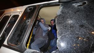 Pro-Ukraine protesters shelter inside a police bus during clashes with pro Russia protesters following a rally in Donetsk