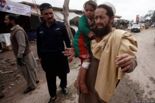A resident carries his daughter, who was injured in a bomb blast, as they evacuate a site of a bomb blast on the outskirts of Peshawar