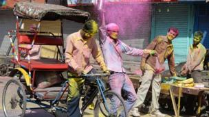 Indian revellers, cover each other with coloured powder, as they celebrate Holi, the Festival of Colours in the old quarters of New Delhi on 17 March 2014