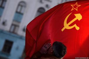 A man kisses the Soviet Union flag in Simferopol's Lenin Square