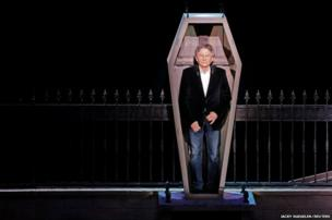 Film director Roman Polanski stands inside a coffin