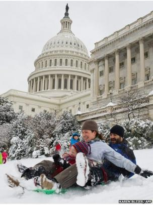 A family slides down the hill at the US Capitol in Washington, DC