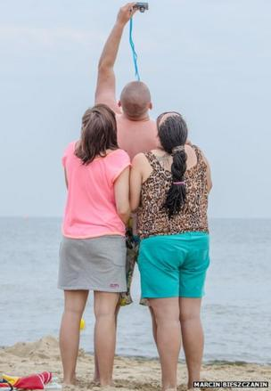A man takes a photograph of himself and two women