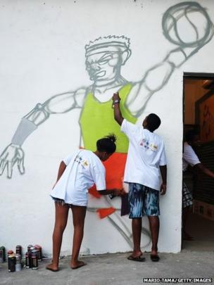 Young graffiti artists paint during an exhibition at the Museu da Mare in Rio de Janeiro, Brazil.