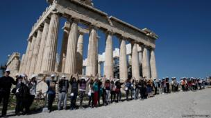 Schoolchildren hold hands as they make a human chain around the Parthenon in Athens