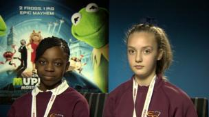 Two School Reporters face the camera