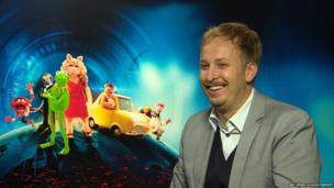 James Bobin in front of Muppets poster