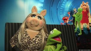 Miss Piggy with her arm around Kermit's neck
