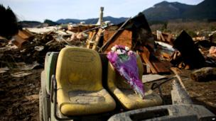 A floral tribute to the dead left at the site of the landslide
