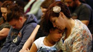 A woman hugs her young daughter during a prayer service at a local church