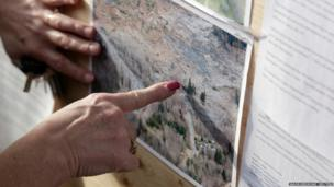 Brenda Neal inspects aerial photos of a massive landslide for any signs of her missing husband in Darrington, Washington