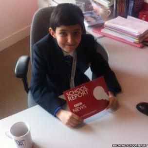 Zakaria from Walworth Academy sits at his desk before presenting his news story