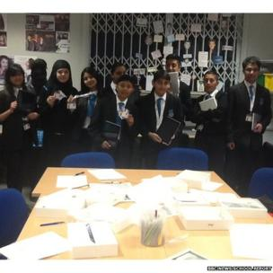Wexham School Reporters stand with their notepads before the camera