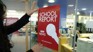 A pupil at The Compton School fixes a BBC School Report poster to a window.
